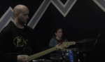 A guitar student and drum student playing Steppin' Stone